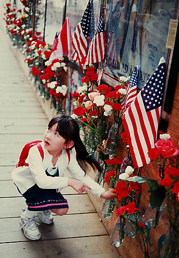 Girl places flowers on Memorial